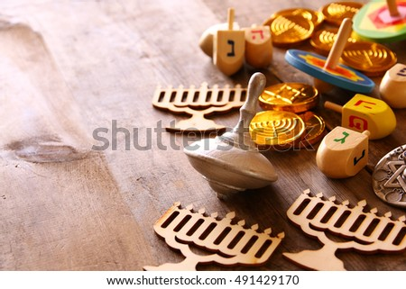 Image of jewish holiday Hanukkah with wooden dreidels colection (spinning top) and chocolate coins on the table