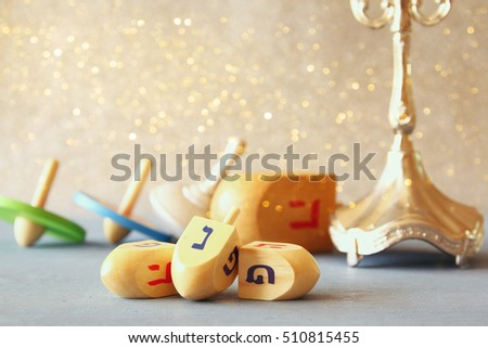 Image of jewish holiday Hanukkah with wooden dreidels colection (spinning top) and chocolate coins on the table. Selective focus - Shutterstock ID 510815455
