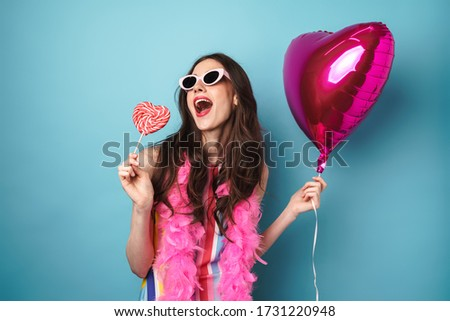Image of joyful brunette woman in sunglasses holding balloon and lollipop isolated over blue background