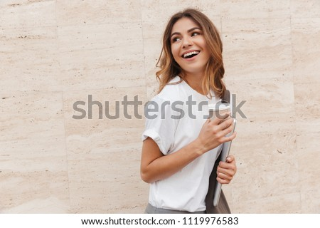 Image of joyful brunette woman walking against beige wall outdoor and looking backward with silver laptop and takeaway coffee in hands