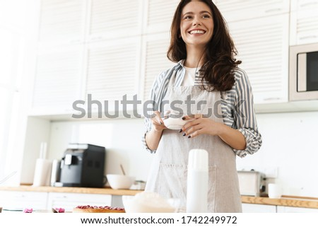 Image of joyful brunette woman wearing apron smiling while cooking pie in modern kitchen stock photo