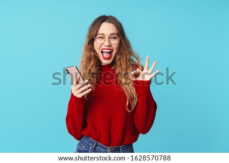 Image of joyful caucasian woman holding cellphone and gesturing ok sign while winking isolated over blue background