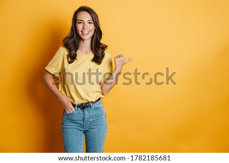 Image of joyful charming woman smiling and pointing finger aside isolated over yellow background