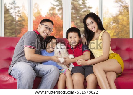 Image of joyful family holding their puppy while sitting on the sofa and smiling at the camera