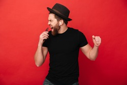 Image of joyous guy wearing black t-shirt and hat singing and listening to music with cell phone and wireless earphones isolated over red wall