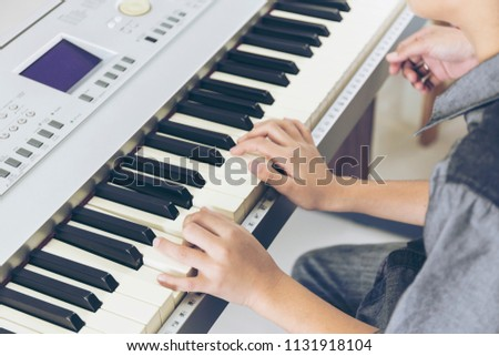 image of kids playing musical instruments. close up hands with keyboard or playing piano, lessons at a music school. Rehearsal, school and discipline concept.  #1131918104