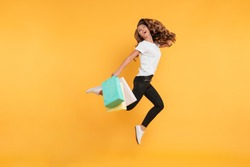 Image of laughing pretty young woman jumping isolated over yellow wall background. Looking aside holding shopping bags.