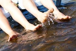 Image of legs of two people splashing water