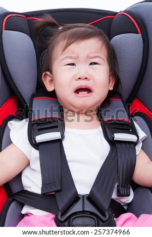 Image of little asian (thai) girl crying and fastened with security belt in safety car-seat. Concept about the safety of traveling by car, children and baby