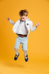Image of little boy child jumping isolated over yellow background. Looking aside.