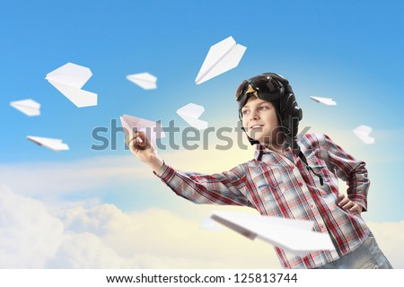 Image of little boy in pilots helmet playing with paper airplane
