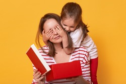 Image of little cute daughter closing eyes of mommy, woman holding red gift box while sitting on floor, charming preschool child girl making surprise for happy mom, present for Mother's Day.