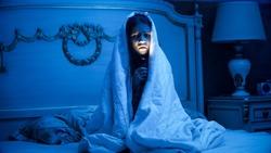 Image of little girl covering under blanket holding flashlight in dark room