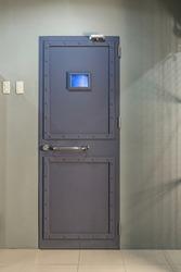 Image of locked metal grey door with window of lab in lost room.