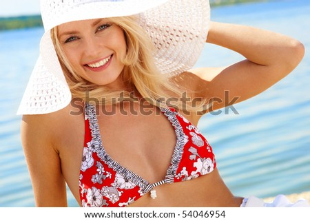 Image of luxurious woman in bikini and hat relaxing on the seashore