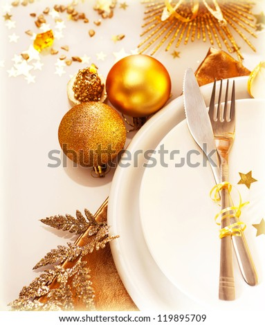 Image of luxury Christmas table setting, festive white dishware served with silver cutlery and decorated with beautiful golden candle and shiny bauble, New Year holiday, xmas celebration