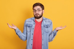 Image of magnetic handsome helpless young man shrugging with shoulders, looking directly at camera, raising arms, having confused facial expression, wearing casual clothes. Emotions concept.