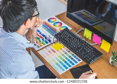 Image of male creative graphic designer working on color selection and drawing on graphics tablet at workplace with work tools and accessories in workspace. #1248031198