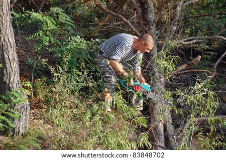 Image of male cutting wood with chainsaw.Ukraine