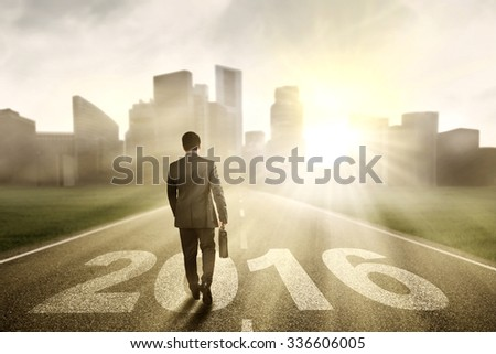Image of male entrepreneur walking on the road with numbers 2016 while carrying suitcase #336606005
