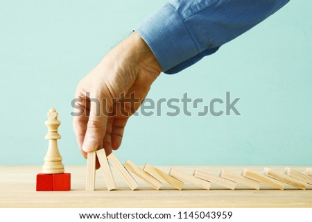 image of male hand stopping the domino effect. executive and risk control concept #1145043959