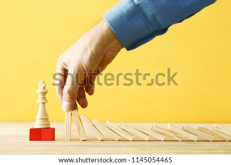 image of male hand stopping the domino effect. executive and risk control concept #1145054465