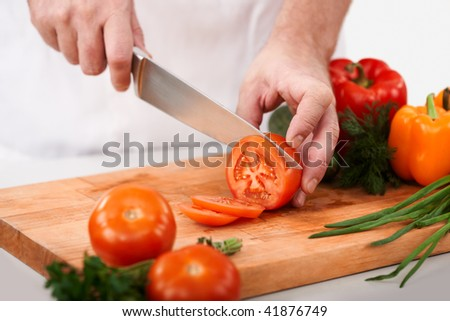 Image of male hand with knife cutting tomatoes on wooden chopping board