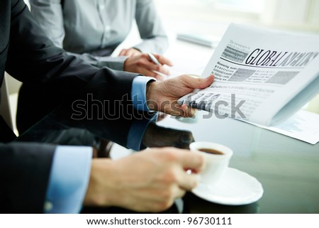 Image of male hand with newspaper and cup of coffee
