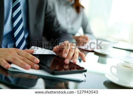 Image of male hands with digital tablet touching its screen