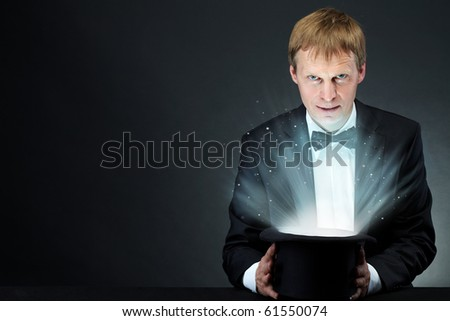 Image of male magician holding hat with magic light and looking at camera
