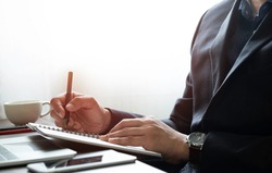 image of man hand using writing pen memo on notebook paper or letter, diary on table desk office. Workspace, working project creative idea for job. business working and learning education concept.