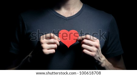 Image of man holding red paper heart cutout