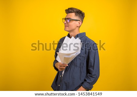 Image of  man in glasses  posing isolated over yellow wall background. People, business, job, profession and occupation. Ofice workerthrowing paper sheets up in the air after he failed project