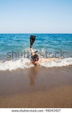 Image of man in goggles and flippers lying in the sea and doing splashing