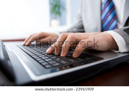 Image of man?s hands pushing buttons of keyboard in the office