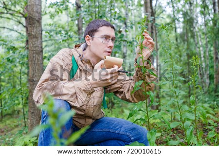 Image of man with notebook and pencil studying plant ストックフォト ©