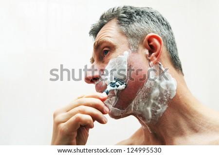 Image of mature man shaving