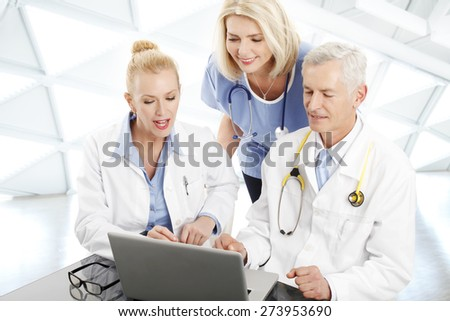 Image of medical staff consulting while sitting at desk in front of laptop at private clinic. Doctors and nurse analyzing the result of medical tests.
