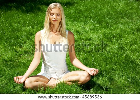 Image of meditating girl seated in pose of lotus on green grass