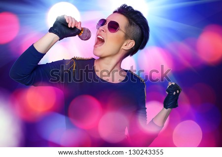 Image of modern rock singer who is screaming on the microphone during the photoset
