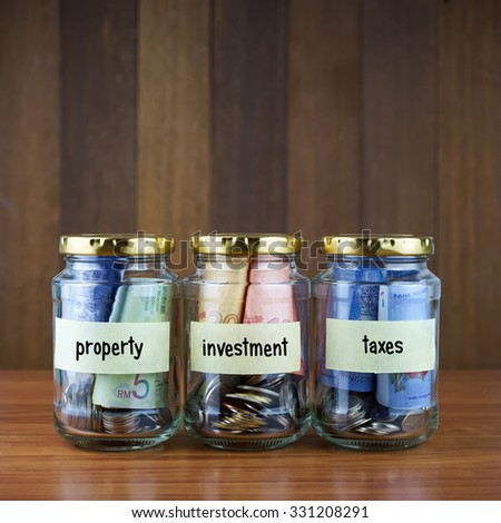 Image of money in clear bottles with PROPERTY, INVESTMENT, TAXES labels against blurred wooden background. Saving concept.