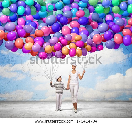 Photo of Image of mother and son holding bunch of colorful balloons