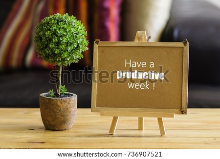 Image of motivational greeting have a productive week on brown mini notice board. Besides a decorative green plant in vase. Selective focus on notice board. Others in gradient blur.