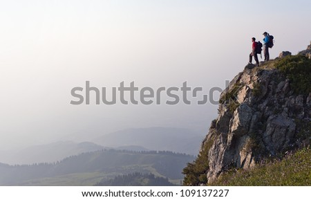 Photo of Image of mountain scenery, on top of which stands the silhouette of a tourist couple, who enjoys success achieved heavy climbing.