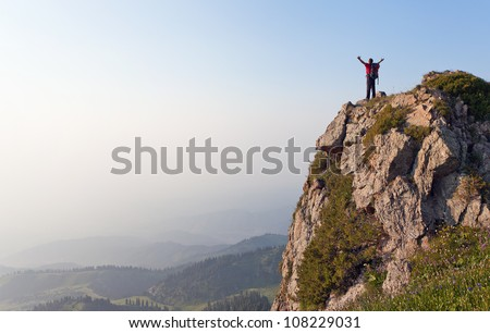 Image of mountain scenery, on top of which stands the silhouette of a tourist with his hands up, who enjoys success achieved heavy climbing.