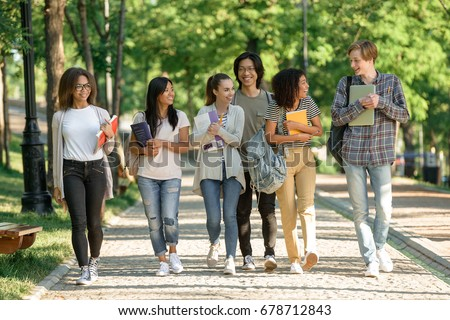 Image of multiethnic group of happy young students walking outdoors. Looking aside.