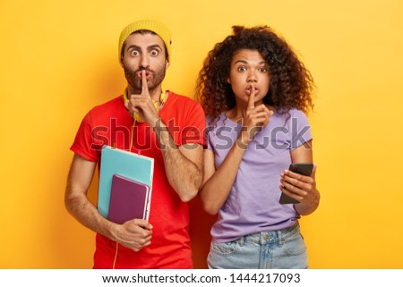 Image of multiethnic teenage friends show silence gesture, ask keep information confidential, use cell phone for chatting online, gossip about groupmates, isolated on yellow background. Omg, be silent