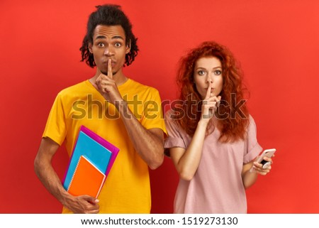 Image of multiethnic teenage friends show silence gesture, ask keep information confidential, use cell phone for chatting online, gossip about groupmates, isolated on red background. Omg, be silent