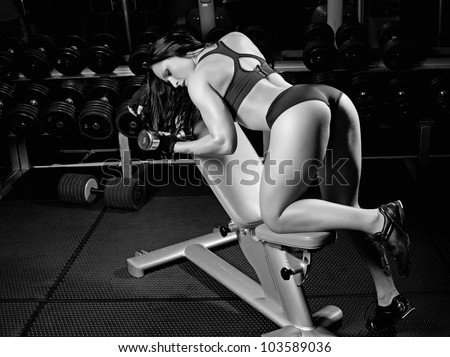 Image of muscle girl with dumbbells in gym