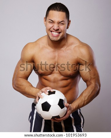 Image of muscle man posing in studio with ball